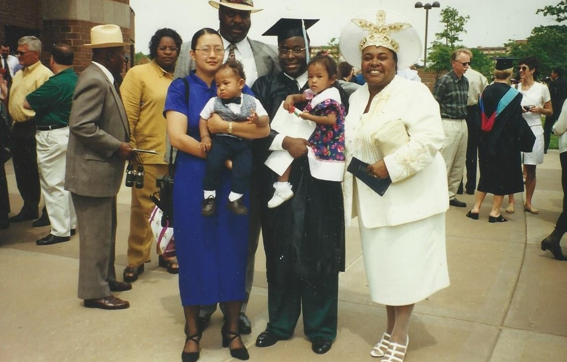 Jarius Jones (in commencement cap and gown) celebrates his KU Bachelor of Science in Education graduation with his family in May 1999 in Lawrence, Kansas. From left: Wife Kim Jones holding their son Jarius Jones II and expecting their daughter Olivia, Jarius Jones holding their daughter Mija Jones, and Jarius' mother Velma Jones. Behind Kim and Jarius is Jarius' father Ted S. Jones. Jarius' grandfather Olvin Burns and sister Karene Jones-Salaam, who earned her master's degree in engineering management from KU, look on in the background.