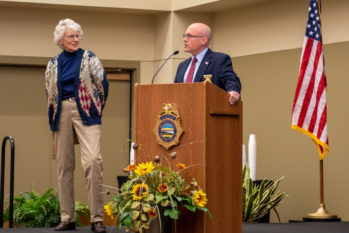 KLETC Executive Director Darin Beck delivers remarks at Beckie Miller's retirement celebration before presenting her a letter from KU Provost Carl Lejuez and Chancellor Douglas A. Girod granting her Emeritus status.