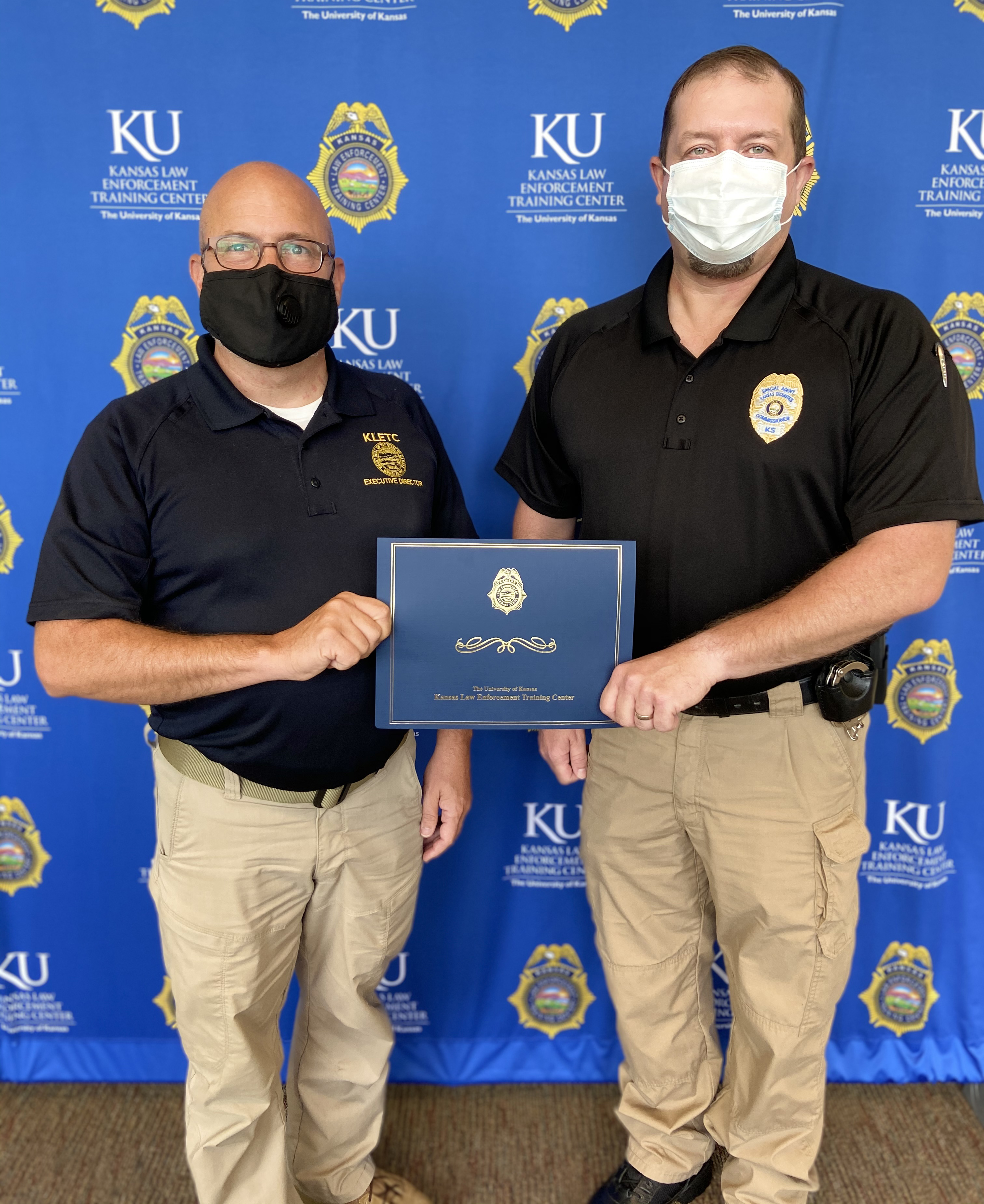 Ryan Morton, Special Agent with the Kansas Securities Commission, poses with his certificate with KLETC Executive Director Darin Beck.